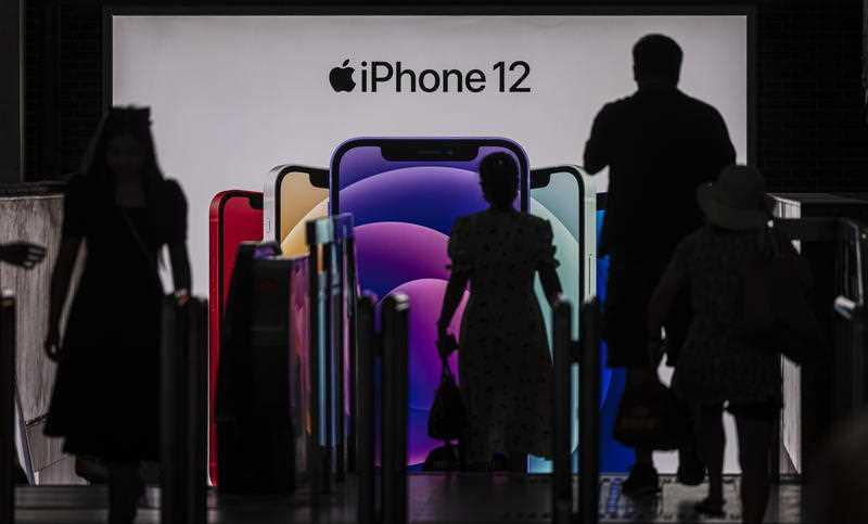 People enter the subway in front of a Apple's iPhone 12 advertisement, in Shanghai, China.
