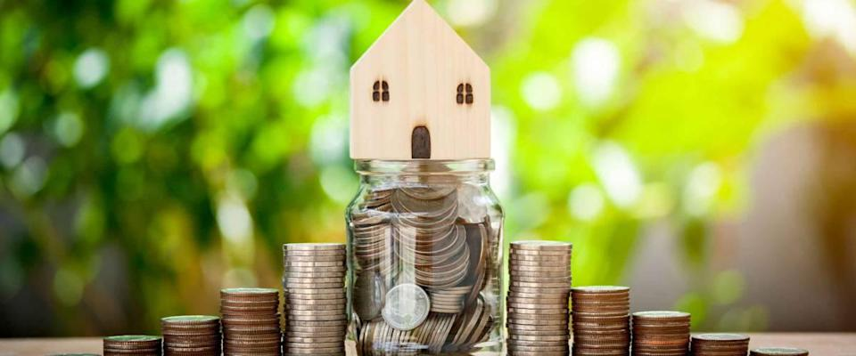 House model on coins and money in a jar for saving concept investment mortgage fund finance and interest rate home loan on bokeh background.