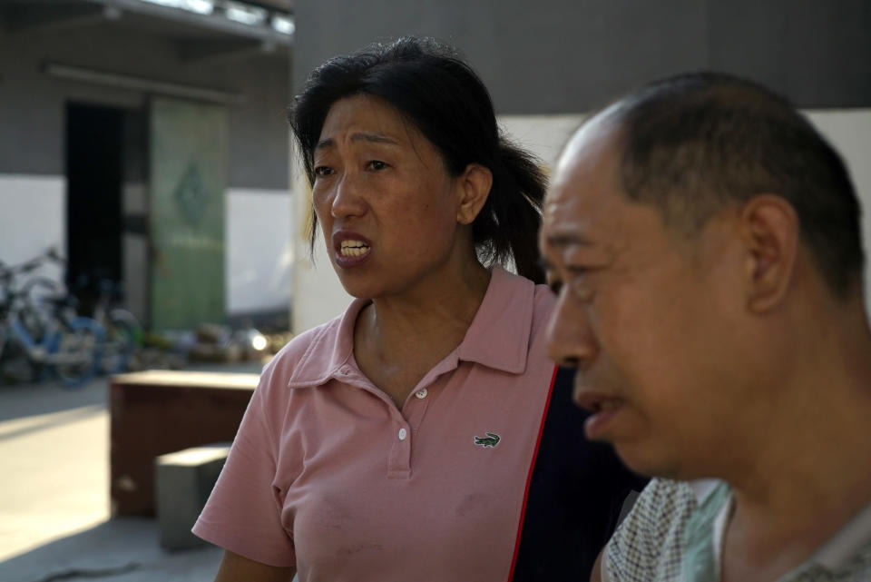 Yu Ruiping, left, and her husband Lu Jinlin, right, stand outside a family warehouse in Xinxiang in central China's Henan Province, Monday, July 26, 2021. Record rain in Xinxiang last week left the couple's goods in a nearby market underwater, causing losses that could run into the tens of thousands of dollars. Dozens of people died in the floods that immersed large swaths of central China's Henan province in water. (AP Photo/Dake Kang)