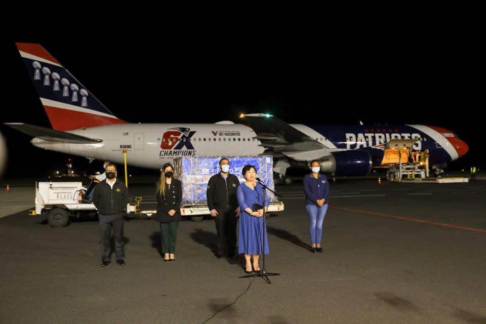 In this photo provided by El Salvador's presidential press office, China's ambassador to El Salvador Ou Jianhong speaks during a ceremony to receive containers of Chinese-made Sinovac COVID-19 vaccines, transported by The New England Patriots team plane, behind, at the airport in San Salvador, El Salvador, late Tuesday, May 18, 2021. (El Salvador's presidential press office via AP)