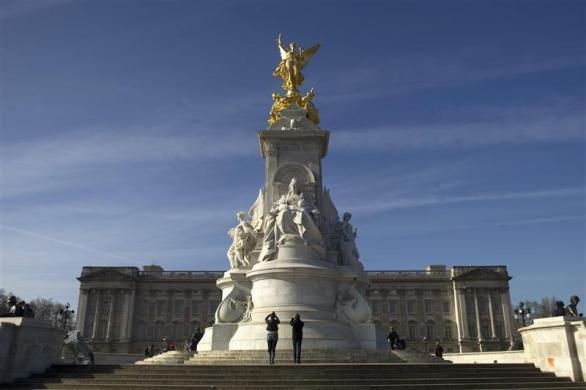 Tourists photograph the Queen Victoria Monument outside Buckingham Palace in London March 8, 2012.