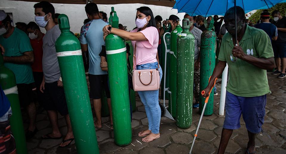 People stand in line holding oxygen canisters in Brazil. Source: AP