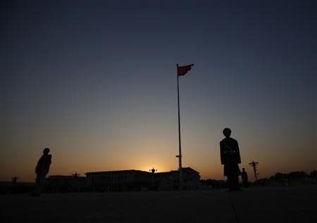 A paramilitary policeman stands guard next to the Chinese national flag on Tiananmen square as the sun sets behind the Great Hall of the People (background), where the closing ceremony of the Chinese Communist Party plenum is going to be held on Tuesday, in Beijing, November 11, 2013. REUTERS/Kim Kyung-Hoon
