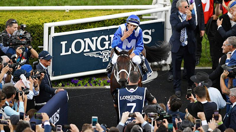 Jockey Hugh Bowman celebrates on the back of champion race horse Winx after her final victory in 2019.