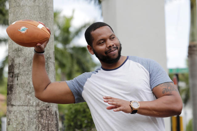 In this Tuesday, June 16, 2020 photo, D.J. Boldin throws a football outside of his home in Miramar, Fla. Boldin is the football coach at Pahokee High School, a predominantly black school located alongside Lake Okeechobee in Florida. Recent events have given Boldin an opportunity to use his position to prepare his players for the challenges they will face when they leave the bubble that is their small town. (AP Photo/Lynne Sladky)