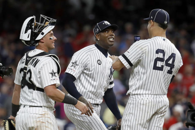 American League pitcher Aroldis Chapman, of the New York Yankees, jokes with teammate Gary Sanchez (24), of the New York Yankees, and James McCann, left, of the Chicago White Sox, after the American League defeated by National League 4-3 in the MLB baseball All-Star Game, Tuesday, July 9, 2019, in Cleveland. (AP Photo/John Minchillo)