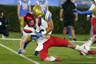 Arizona quarterback Grant Gunnell, bottom, is tackled by UCLA linebacker Bo Calvert after throwing during the first half of an NCAA college football game Saturday, Nov. 28, 2020, in Pasadena, Calif. (AP Photo/Marcio Jose Sanchez)