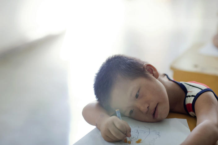 In this photo taken Aug. 7, 2012, Vo Hong Vu tries to draw some animals at a rehabilitation center in Danang, Vietnam. The children were born with profound physical and mental disabilities that the center's director said were caused by their parents' exposure to the chemical dioxin in the defoliant Agent Orange. Washington was slow to respond, but on Thursday, Aug. 9, 2012 the U.S. for the first time will begin cleaning up leftover dioxin that was stored at the former military base, now part of Danang's airport. (AP Photo/Maika Elan)