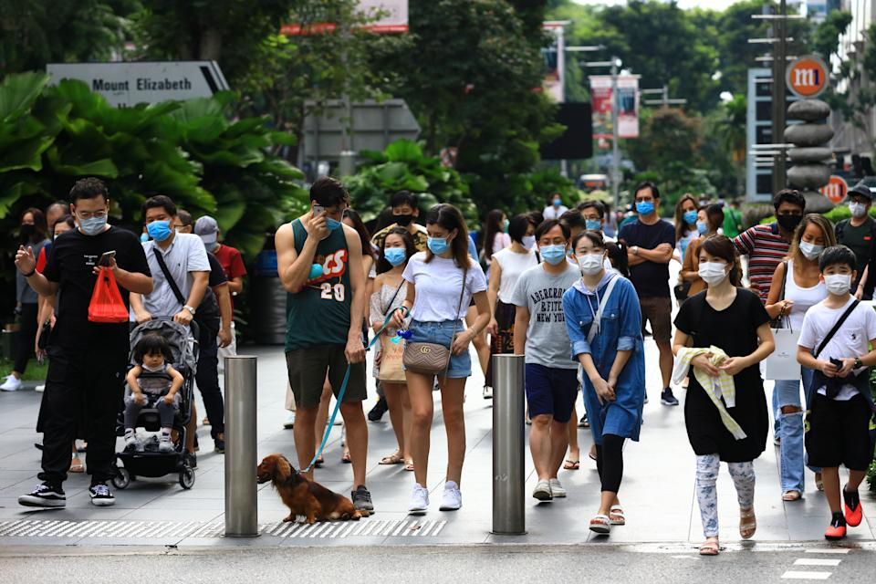 SINGAPORE - JUNE 20:  People wearing protective masks wait to cross a street at Orchard Road shopping belt on June 20, 2020 in Singapore. From June 19, Singapore started to further ease the coronavirus (COVID-19) restrictions by allowing social gatherings up to five people, re-opening of retail outlets and dining in at food and beverage outlets, subjected to safe distancing. Parks, beaches, sports amenities and public facilities in the housing estates will also reopen. However, large scale events, religious congregations, libraries, galleries and theatres will remain closed.  (Photo by Suhaimi Abdullah/Getty Images)
