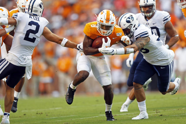 Tennessee running back Ty Chandler (8) runs for yardage as he's hit by Brigham Young linebacker Jackson Kaufusi (38) in the first half of an NCAA college football game Saturday, Sept. 7, 2019, in Knoxville, Tenn. (AP Photo/Wade Payne)