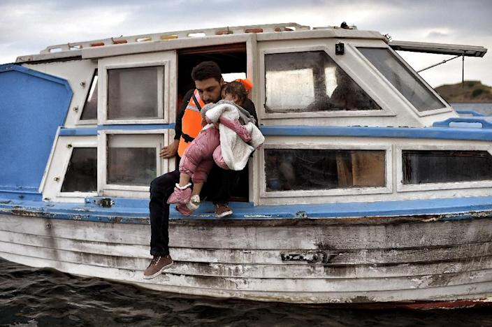 A man carrying a child gets off a boat as migrants arrive at the Greek island of Lesbos on September 29, 2015 (AFP Photo/Aris Messinis)