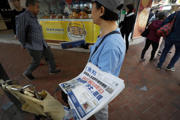 """A vendor gives out copies of newspaper with a headlines of """"Wuhan break out a new type of coronavirus, Hong Kong prevent SARS repeat"""" at a street in Hong Kong, Saturday, Jan. 11, 2020. Health authorities in the central Chinese city of Wuhan are reporting the first death from a new type of coronavirus. The Wuhan Municipal Health Commission reported Saturday that seven other people are in critical condition. (AP Photo/Andy Wong)"""