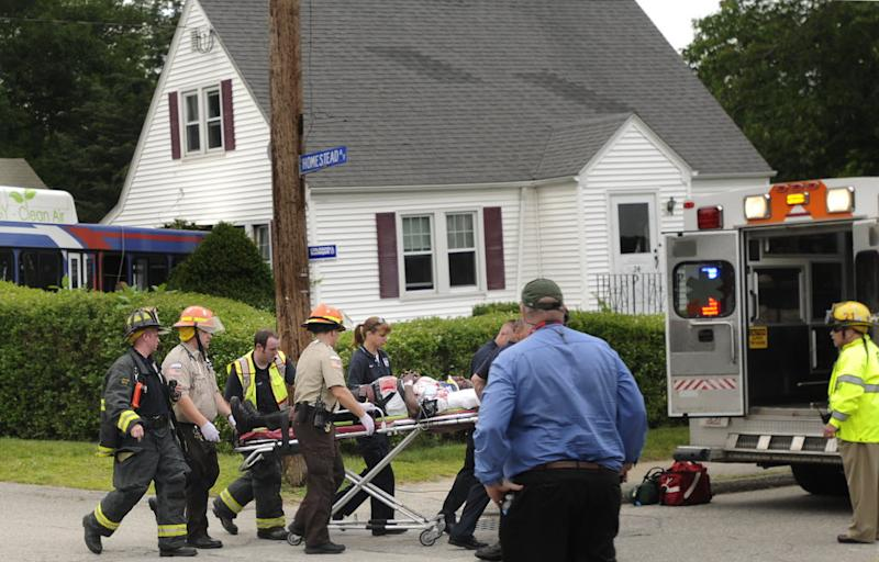 The driver of a Worcester Regional Transit Authority Bus is wheeled to a waiting ambulance Monday, June 24, 2013, after the bus crashed into a house in Auburn, Mass. Fire Capt. Eric Otterson said the driver, who was trapped for more than an hour after the 5 p.m. crash, was seriously hurt. He was taken to a hospital. (AP Photo/Worcester Telegram & Gazette, Christine Peterson)