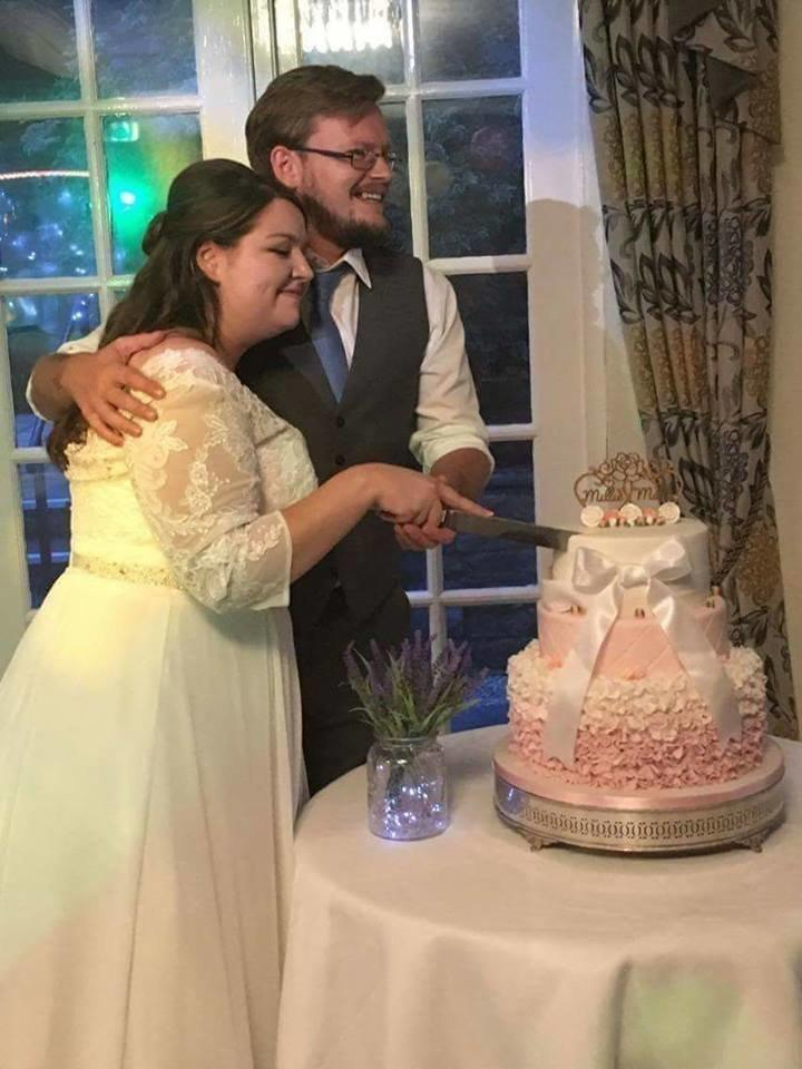 The newlyweds cutting the repaired cake.  (Courtesy of Millie Maltby)