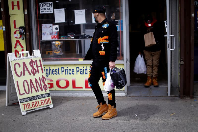 Men leave pawn shop offering loans during outbreak of coronavirus disease (COVID-19) in Bronx borough of New York