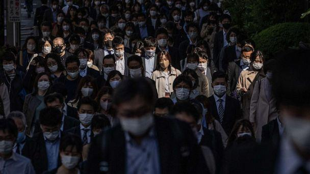 PHOTO: People wearing face masks to protect against COVID-19 walk to work in Tokyo, Japan, on April 23, 2021. (Carl Court/Getty Images)