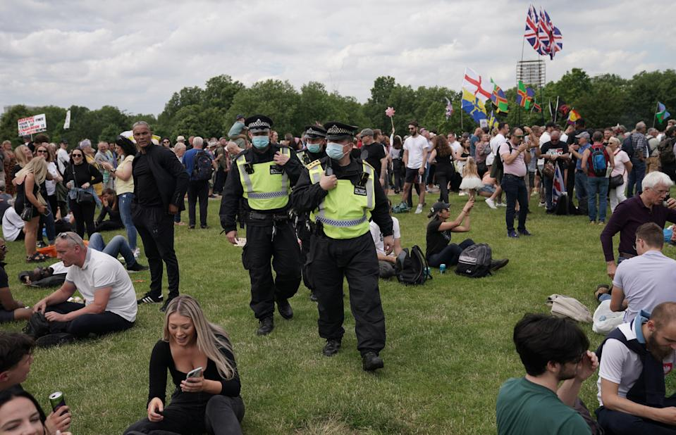 Police officers look on as protesters gather in Hyde Park (PA)