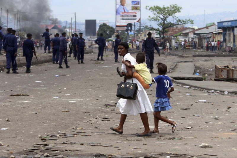 FILE - In this Sept 19, 2016 file photo shot by AP contributing photographer John Bompengo, a family pass near Congolese riot police during a protest in Kinshasa, Democratic Republic of Congo. Relatives say longtime Associated Press contributor John Bompengo has died of COVID-19 in Congo's capital. Bompengo, who had covered his country's political turmoil over the course of 16 years, died Saturday, June 20, 2020 at a Kinshasa hospital. (AP Photo/John Bompengo, file)