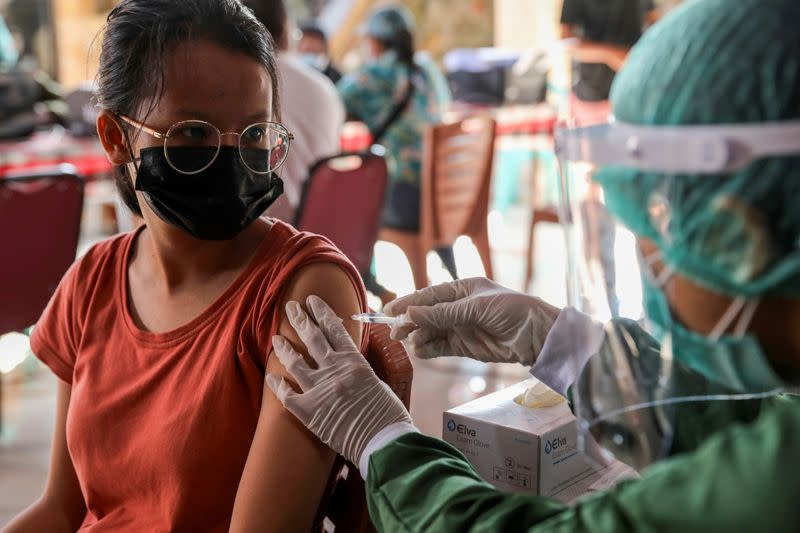 FILE PHOTO: A woman receives a dose of AstraZeneca COVID-19 vaccine during a mass vaccination programme for Green Zone Tourism in Sanur, Bali, Indonesia,