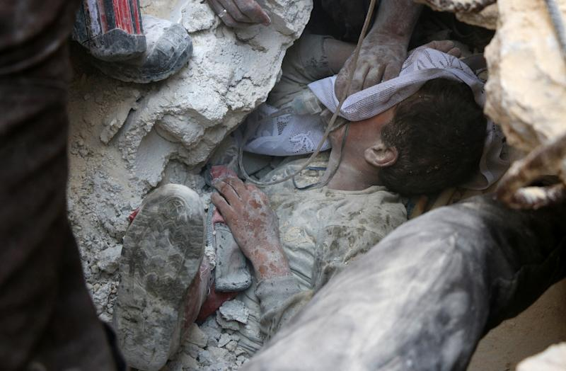 Jameel Mustafa Habboush, a 13-year-old Syrian boy receives oxygen as he is pulled from the rubble of a building following Russian air strikes on the northern embattled Syrian city of Aleppo on October 11, 2016 (AFP Photo/Thaer Mohammed)