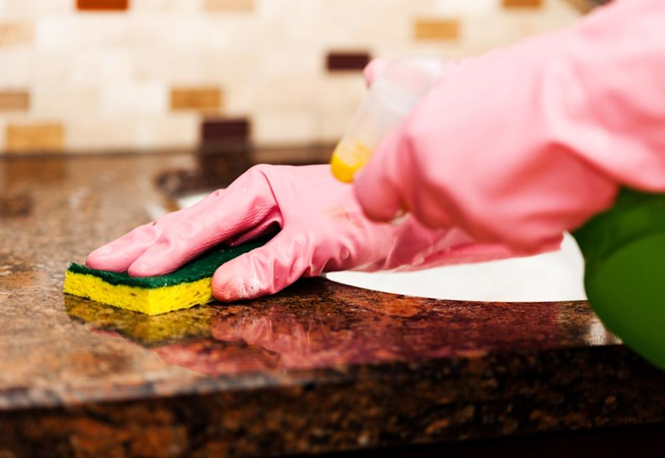 Woman cleaning counter top in the kitchen