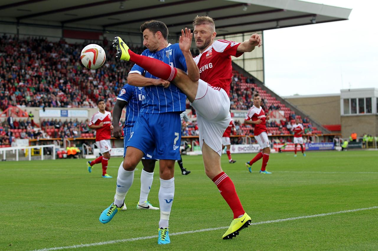 Gillingham's Chris Whelpdale is challenged by Swindon's Darren Ward during the Sky Bet Football League One match at the County Ground, Swindon.