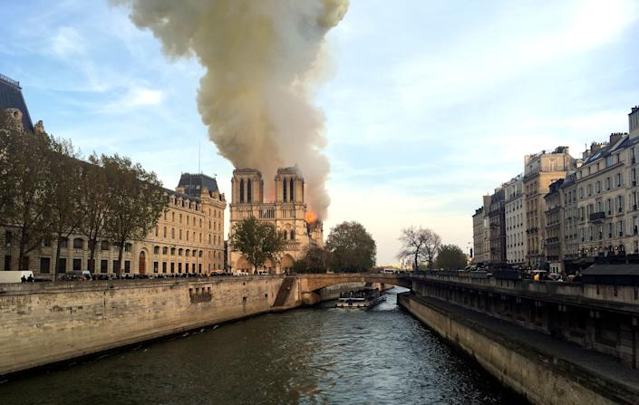 Notre Dame cathedral is burning in Paris, Monday, April 15, 2019. Massive plumes of yellow brown smoke is filling the air above Notre Dame Cathedral and ash is falling on tourists and others around the island that marks the center of Paris. (Photo: Lori Hinant/AP)