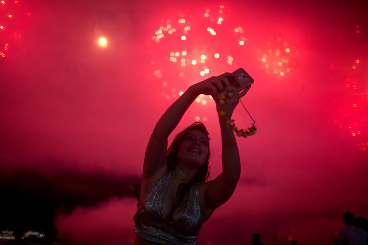 A woman takes a selfie during New Year's celebrations at Copacabana beach in Rio de Janeiro on January 1, 2018. (Photo: MAURO PIMENTEL via Getty Images)