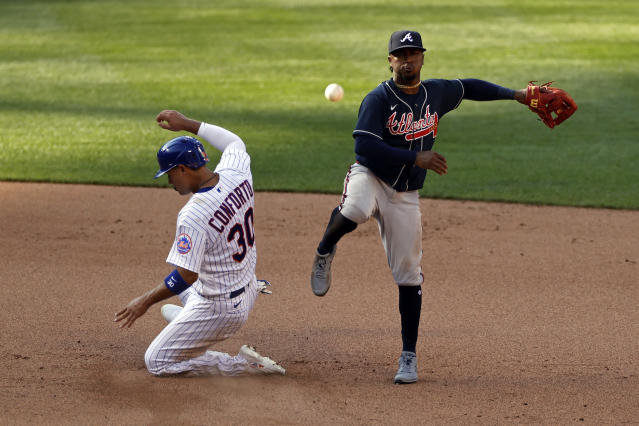 Atlanta Braves second baseman Ozzie Albies turns a double play against New York Mets' Michael Conforto (30) during the seventh inning of a baseball game Saturday, July 25, 2020, in New York. (AP Photo/Adam Hunger)