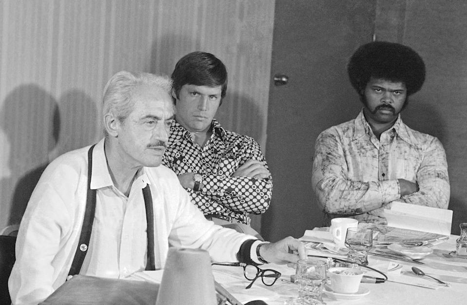 FILE - In this Saturday, March 13, 1976, file photo, Marvin Miller, executive director of the baseball players association, holds a news conference in St. Petersburg, Fla., as New York Mets pitcher Tom Seaver, rear left, and St. Louis Cardinals' Reggie Smith look on. The 1970s. Players of color finally stepping into an unfettered spotlight, the reserve clause ending, free agency beginning and the players' union finding its voice. (AP Photo/File)