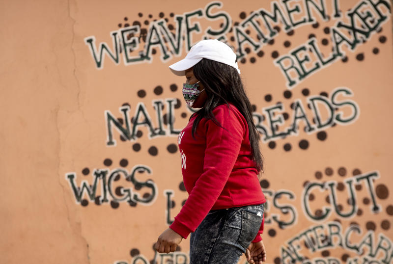 A woman wearing a face mask to protect herself against coronavirus, walks past a closed hair salon at Tembisa township in Johannesburg, South Africa, Tuesday, May 19, 2020. (AP Photo/Themba Hadebe)