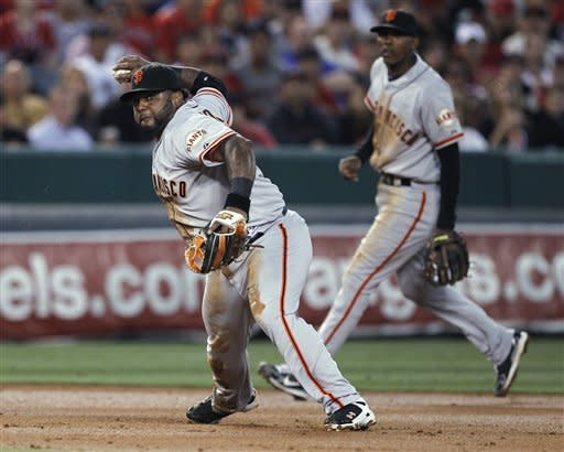 San Francisco Giants third baseman Pablo Sandoval fails to throw Los Angeles Angels' Erick Aybar out at first as shortstop Joaquin Arias watches during the third inning of a baseball game in Anaheim, Calif., Tuesday, June 19, 2012. (AP Photo/Chris Carlson)