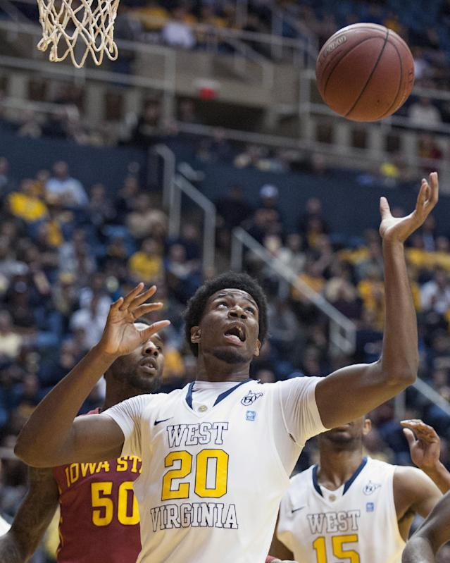 West Virginia's Brandon Watkins (20) goes for a rebound during the first half of an NCAA college basketball game against Iowa State, Monday, Feb. 10, 2014, in Morgantown, W.Va. (AP Photo/Andrew Ferguson)
