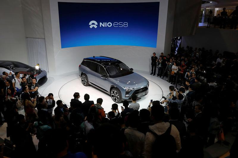 People gather at the booth of Chinese electric vehicle start-up Nio as it unveils its ES8 SUV at the Shanghai autoshow, in Shanghai