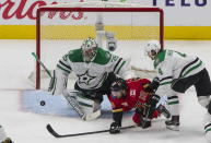 Calgary Flames' Derek Ryan (10) is stopped by Dallas Stars goalie Anton Khudobin (35) as Stars' Miro Heiskanen (4) defends during first-period NHL Western Conference Stanley Cup hockey playoff action in Edmonton, Alberta, Sunday, Aug. 16, 2020. (Jason Franson/The Canadian Press via AP)