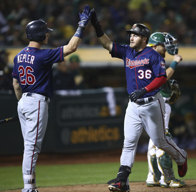 Minnesota Twins' Robbie Grossman, right, celebrates with Max Kepler after hitting a two-run home run off Oakland Athletics' Lou Trivino during the sixth inning of a baseball game Friday, Sept. 21, 2018, in Oakland, Calif. (AP Photo/Ben Margot)