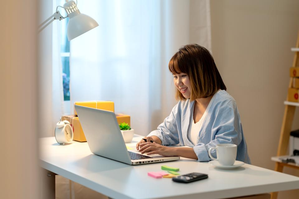Candid of happy young attractive asian woman work at home in evening or late night with SME business owner, young entrepreneur or freelance concept. Young asian student study online in self education.