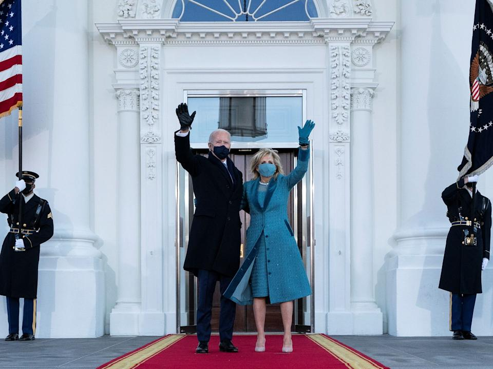 Joe Biden and Jill Biden wave as they arrive at the North Portico of the White House, which has had its 132 rooms deep cleaned since Donald Trump's departure in light of the coronavirus pandemicREUTERS