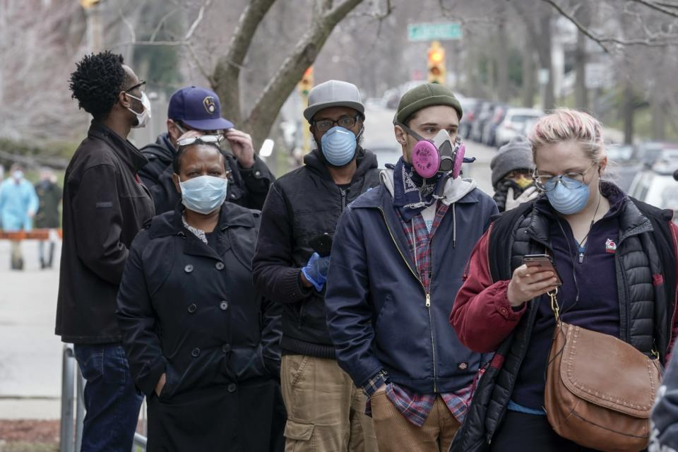 FILE - In this April 7, 2020, file photo, voters masked against coronavirus line up Wisconsin's primary election in Milwaukee. Wisconsin Gov. Tony Evers has issued a new statewide mask order an hour after the Republican-controlled Legislature voted to repeal his previous mandate on Thursday, Feb. 4, 2021. The Democrat Evers said in a video message Thursday that his priority is keeping people safe and that wearing a mask was the most basic way to do that. (AP Photo/Morry Gash, File)