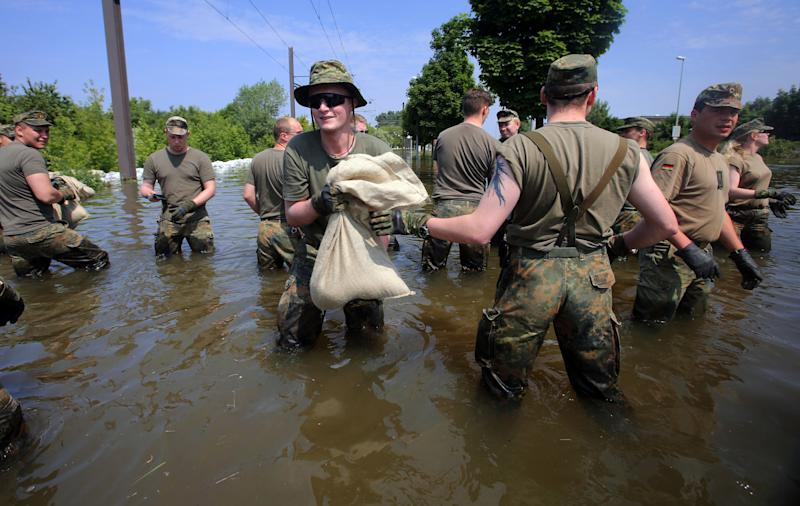 German army soldiers work at a dike in the city of Magdeburg, eastern Germany, Sunday June 9, 2013.   Thousands of people have been evacuated from their homes in a region of eastern Germany where the Elbe river has flooded and burst through a dam, officials said Sunday. More than 20  people have been killed by a week of flooding in central Europe, as rivers such as the Danube, the Elbe and the Vlatava have overflowed after heavy rains and caused extensive damage in central and southern Germany, the Czech Republic, Austria, Slovakia and Hungary. (AP Photo/dpa, Jens Buettner)