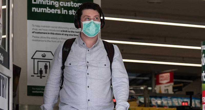 Photo shows customer leaving a Woolworths store leaving wearing a mask.
