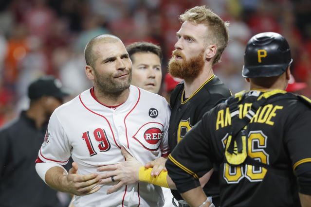 Cincinnati Reds first baseman Joey Votto (19) is restrained by Pittsburgh Pirates third baseman Colin Moran, center, during the ninth inning of a baseball game Tuesday, July 30, 2019, in Cincinnati. (AP Photo/John Minchillo)