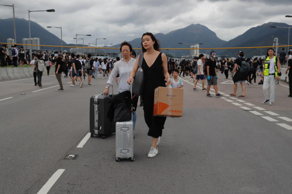 Passengers walk to airport as pro-democracy protestors blocked a road outside the airport in Hong Kong, Sunday, Sept.1, 2019. Train service to Hong Kong's airport was suspended Sunday as pro-democracy demonstrators gathered there, while protesters outside the British Consulate called on London to grant citizenship to people born in the former colony before its return to China. (AP Photo/Kin Cheung)