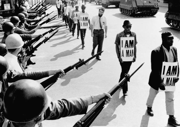 Civil rights activists are blocked by National Guards wielding bayonets while trying to stage a protest on Beale Street in Memphis, Tennessee.  Protesters marching, carrying signs indicating