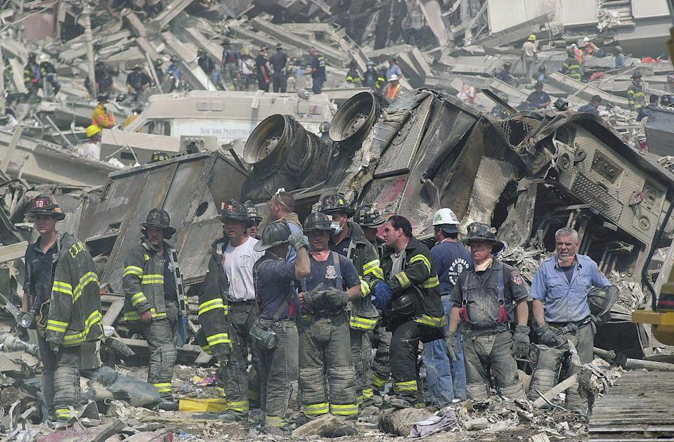 New York City firefighters take a break near a demolished ladder truck in the remains of the World Trade Center on Sept. 12, 2001.