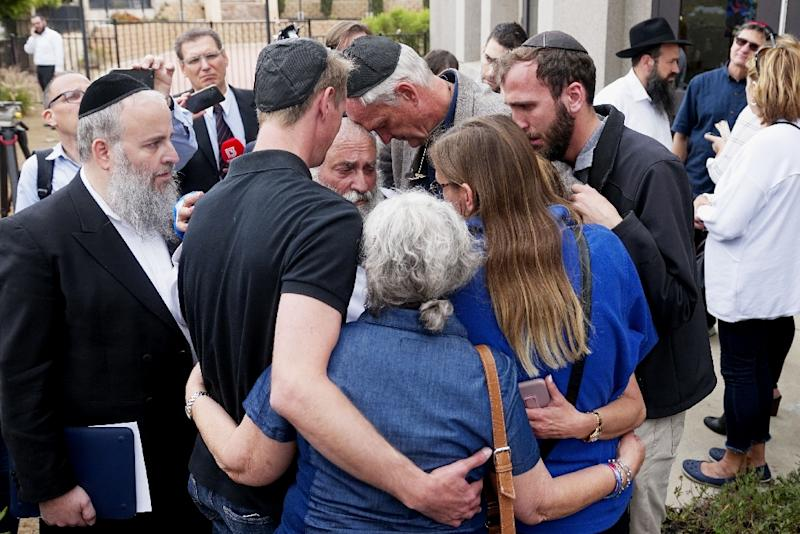 The Chabad of Poway congregation console one another after a teenage gunman stormed their synagogue on the last day of Passover, killing one and wounding three (AFP Photo/SANDY HUFFAKER)