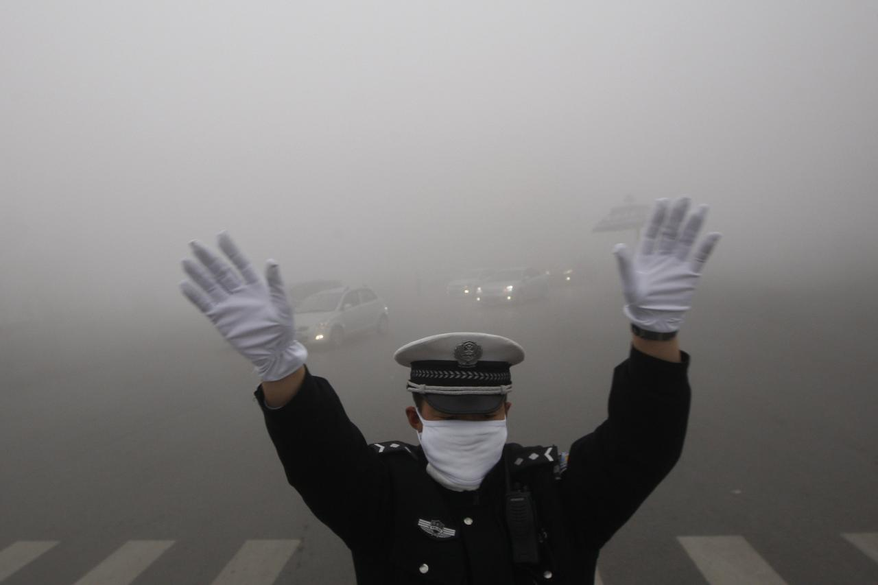 A traffic policeman signals to drivers during a smoggy day in Harbin, Heilongjiang province, October 21, 2013. The second day of heavy smog with a PM 2.5 index has forced the closure of schools and highways, exceeding 500 micrograms per cubic meter on Monday morning in downtown Harbin, according to Xinhua News Agency. REUTERS/China Daily (CHINA - Tags: ENVIRONMENT TRANSPORT) CHINA OUT. NO COMMERCIAL OR EDITORIAL SALES IN CHINA