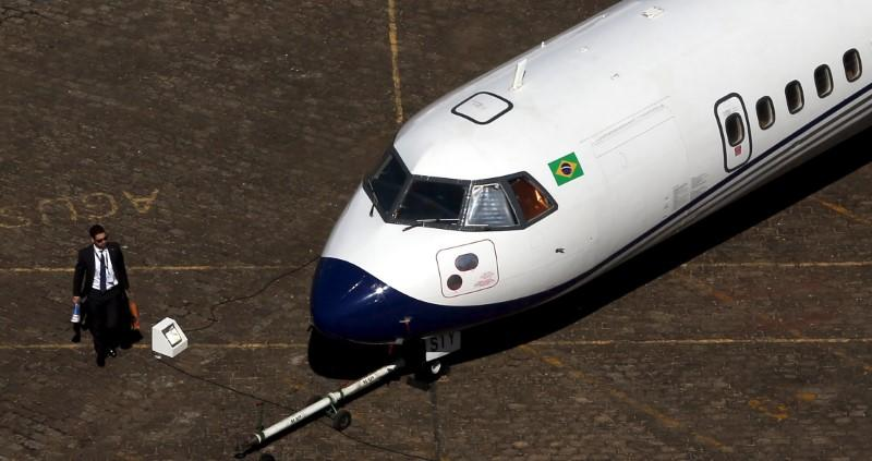 A man walks past an ATR aircraft during the LABACE at Congonhas Airport in Sao Paulo
