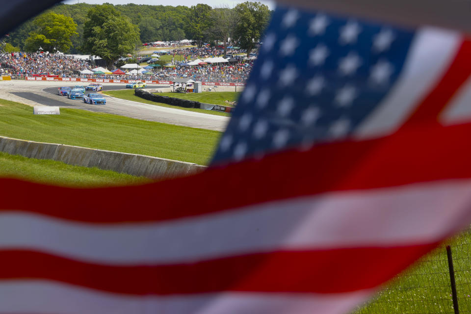 Cars make a turn during a NASCAR Cup Series auto race Sunday, July 4, 2021, at Road America in Elkhart Lake, Wis. (AP Photo/Jeffrey Phelps)