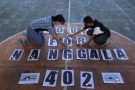 Students arrange the candles during a vigil for crew members who onboard the submarine KRI-402, sunk at the north Bali sea during a drill, in Banyuwangi